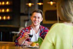 Ung man och kvinna som dricker vin i en restaurang Ung man och kvinna som dricker vin på ett datum Man och kvinna på ett datum Arkivfoton