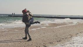 Ung man och kvinna som går på stranden Par på havet på den kalla vinterdagen stock video