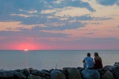 Ung man och kvinna som möter solnedgången på kusten för baltiskt hav royaltyfri foto
