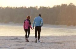 Ung man och kvinna som promenerar stranden arkivbild