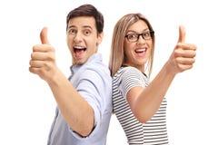 Ung man och kvinna som rymmer upp deras tummar Arkivfoton