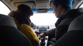Ung man och kvinna som sitter i bilen Mannen förklarar henne hur man startar bilen arkivbilder
