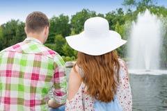 Ung man och kvinna som sitter mitt emot den konstgjorda sjön i PA fotografering för bildbyråer