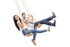 Ung man och kvinna som svänger på gungor Fotografering för Bildbyråer