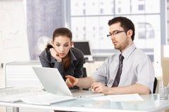 Ung man och kvinna som tillsammans i regeringsställning arbetar arkivfoto