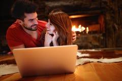Ung man och kvinnlig hållande ögonen på film på bärbara datorn arkivbild