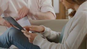 Ung man och kvinnlig som räknar upp kostnader för att starta upp familjeföretag, risker arkivfilmer