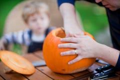 Ung man- och litet barnpojke som gör halloween pumpa Arkivfoton