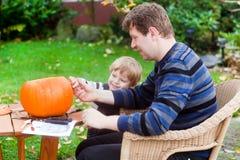 Ung man- och litet barnpojke som gör halloween pumpa Royaltyfria Bilder