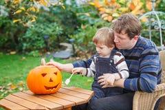 Ung man- och litet barnpojke som gör halloween pumpa Royaltyfri Foto
