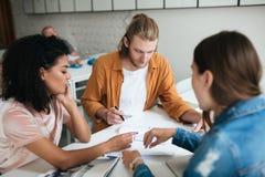 Ung man och två flickor som tillsammans i regeringsställning arbetar Grupp av studenter som tillsammans studerar i klassrum lyckl royaltyfria foton