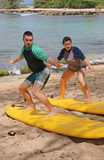 Ung man och ung kvinna som lär att surfa Royaltyfria Foton