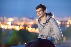 Ung man på bakgrunden nattstaden Arkivbild