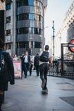 Ung man på en skateboardridning på en trottoar i staden av Lo royaltyfri fotografi