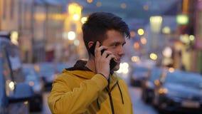 Ung man på mobiltelefonen i gatorna av dinglen arkivfilmer