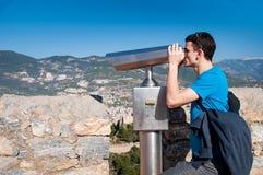 Ung man på observationsdäcket som ser panoramautsikt med kikare Arkivfoto