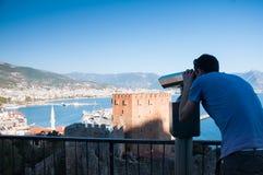 Ung man på observationsdäcket som ser panoramautsikt med kikare Arkivbilder