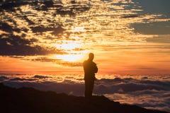 Ung man på solnedgång ovanför molnen i bergen Royaltyfria Bilder