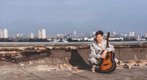 Ung man på taket med en gitarr Fotografering för Bildbyråer