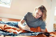 Ung man på säng som drar i färgläggningbok Arkivbilder