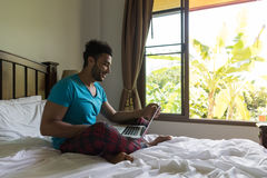 Ung man Sit On Bed, lycklig leendelatinamerikan Guy Bedroom Using Laptop Computer royaltyfri foto