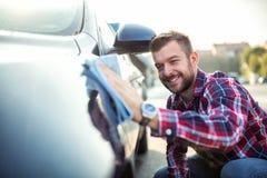 Ung man som är förälskad med hans bil royaltyfri fotografi