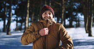 Ung man som är främst av den mycket karismatiska kameran tycka om tiden på naturen på känslan för ampere för snöig skog den stora stock video
