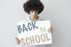 Ung man som är hållande tillbaka till det skriftliga banret för skola Royaltyfria Foton