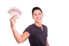 Ung man som är lycklig med pengar i hans händer Royaltyfri Bild