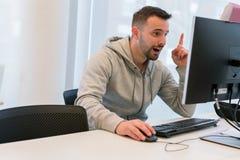 Ung man som är lycklig och upphöjas, därför att han har funnit lösningen framme av datorskärmen royaltyfria foton