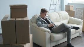 Ung man som är rörd till en ny lägenhet Sitter på soffan med en smartphone arkivfilmer