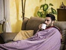 Ung man som är sjuk med influensa som dricker örtte royaltyfri foto