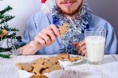Ung man som äter christmanpepparkakakakor Arkivfoto