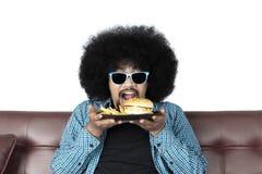 Ung man som äter hamburgare- och fransmansmåfiskar royaltyfri fotografi