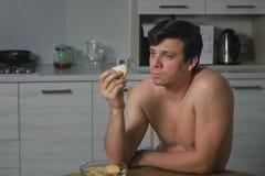 Ung man som äter kakor i köket på natten Sömnlöshet och ångest Överdriven mat arkivfoton