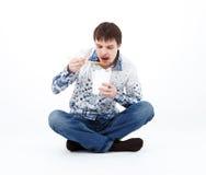 Ung man som äter kinesisk mat från lunchasken med pinnar arkivbilder