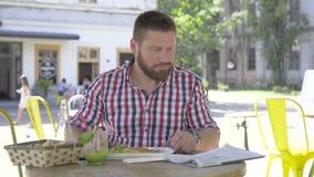 Ung man som äter lunch och den läs- tidningen arkivfilmer