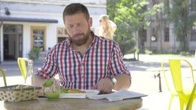 Ung man som äter lunch och läs- tidnings-, glidare- och pannaskottrigh stock video