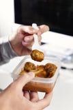 Ung man som äter på kontoret Royaltyfria Foton