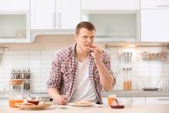 Ung man som äter smakligt rostat bröd med driftstopp på tabellen arkivbild