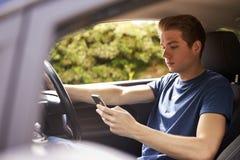 Ung man som överför körning för stund för textmeddelande Arkivfoto