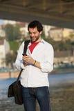Ung man som överför textmeddelandet på mobiltelefonen Royaltyfria Bilder