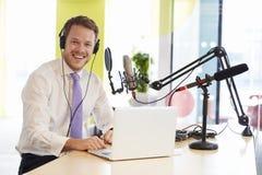 Ung man som antecknar en podcast som ler till kameran, slut upp royaltyfri bild