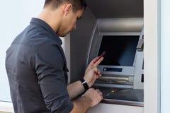 Ung man som använder ATM royaltyfria bilder