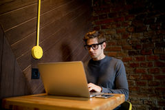 Ung man som använder bärbara datorn i coffee shop med en kopp kaffe Royaltyfri Foto