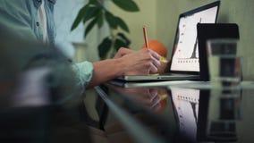 Ung man som använder bärbara datorn i kafé Exponeringsglas av vatten, notepaden och blyertspennan på tabellen lager videofilmer