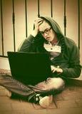 Ung man som använder bärbara datorn i stadsgata Fotografering för Bildbyråer