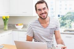 Ung man som använder bärbara datorn, medan ha kaffe Arkivfoto