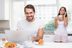 Ung man som använder bärbara datorn på frukosten Royaltyfria Bilder