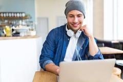 Ung man som använder bärbara datorn på kafét Arkivbild